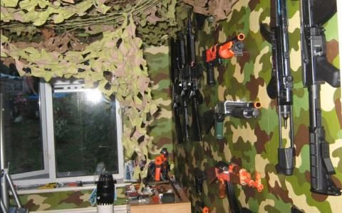 Michael Sandford's bedroom with camouflage netting and toy guns on the wall